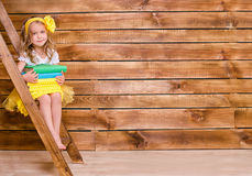 Little girl with stack of books sitting on ladder Royalty Free Stock Photo