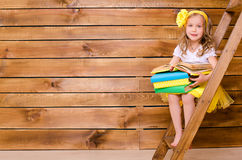Little girl with stack of books sitting on ladder Royalty Free Stock Images