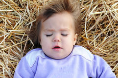 Little girl on stack of hay Royalty Free Stock Photos