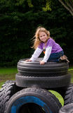 Little girl on stack of  recycled tires Royalty Free Stock Images