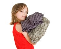 Little girl with stack of sweaters Stock Photos
