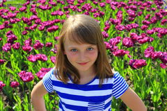 Little girl stand by lilac tulips Stock Images