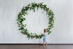 A little girl stand near the wall with big flowers wreath. Rear view Royalty Free Stock Photography