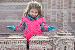 Little girl standing against brick wall while looking at camera Royalty Free Stock Image