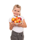 Little girl standing against white backdrop with few fresh necta. You need to get vitamins of fresh fruits from childhood Royalty Free Stock Images