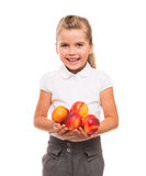 Little girl standing against white backdrop with few fresh necta. You need to get vitamins of fresh fruits from childhood Stock Photography