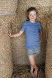 Little girl standing amongst bales of hay Royalty Free Stock Photo