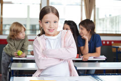 Little Girl Standing Arms Crossed At Desk Royalty Free Stock Images