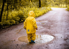Little Girl Standing At A Dirty Puddle Stock Photo
