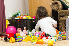 Little girl standing with back in a pile of toys Royalty Free Stock Image