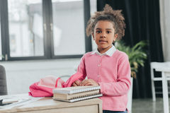 Little girl standing with backpack and looking at camera indoors Royalty Free Stock Photography