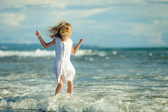 Little girl standing on the beach at the day time Stock Image