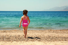 Little girl standing on beach in swimsuit and going to swim Royalty Free Stock Photo