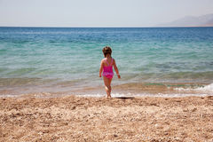 Little girl standing on beach in swimsuit. Rear view. Stock Photo