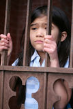 Little girl standing behind iron bars Stock Photo