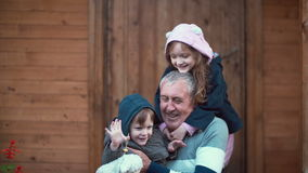 Little girl standing behind old man. Granddaughter hugs grandfather, grandson running to they. Boy sits on man knees. 4K. Little girl standing behind old man Royalty Free Stock Photos