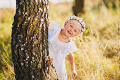 Little girl standing behind a tree in the park outdoors, playing hide and seek, a beautiful white dress Stock Images