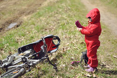 Little girl standing by the bicycle with a child seat Stock Photo