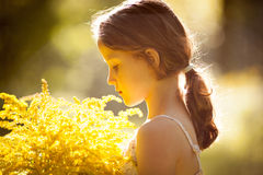 Little girl standing with a bouquet of flowers Stock Images