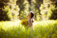 Little girl standing with a bouquet of yellow flowers Stock Images