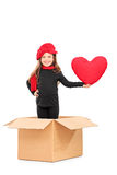 Little girl standing in box with a red heart Royalty Free Stock Image