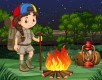 Little girl standing by the campfire Stock Image
