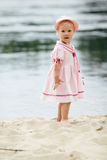 Little girl standing on the coast of river Stock Photos