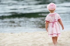 Little girl standing on the coast of river Royalty Free Stock Photos