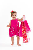 Little girl standing with colorful paper bags isolated on white background. Royalty Free Stock Images