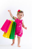 Little girl standing with colorful paper bags isolated on white background. Stock Photo