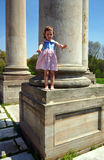 Little girl standing on the column stock photo