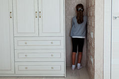 Little girl standing in the corner. Of her room behind the cupboardr Royalty Free Stock Photography