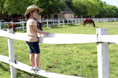 Little girl with standing on corral and watching hors Stock Photography