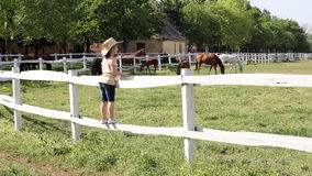 Little girl standing on corral
