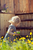 Little girl standing on a country house wooden stairs and holdin Stock Photo