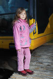 Little girl standing on crawler tractor Royalty Free Stock Photos
