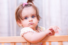Little girl standing in the crib stock photography