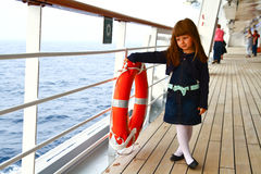 Little girl standing on deck of cruise ship Stock Photos