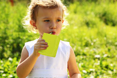 Little girl standing and drinking juice Stock Images