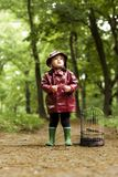Little Girl Standing in Forest Looking for Her Lost Bird. Little beautiful girl dressed in rain coat with flower in her hand standing in forest looking for her royalty free stock photography