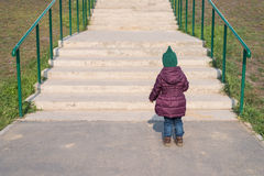 Little girl standing in front of the big staircase stock images