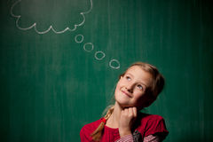 Little girl standing in front of chalkboard with comic cloud dra Stock Photos