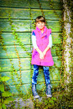 Little girl standing in front of the doors. Little girl standing in front of the green doors royalty free stock image