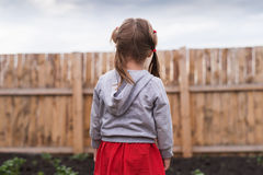 Little girl standing in front of a fence Stock Images