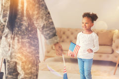 Little girl standing in front of her mother with American flag. Little patriot. Lovely little girl standing in front of her mother wearing a military uniform stock images