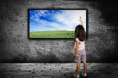 Little girl standing in front of a large monitor Stock Photos