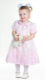 Little girl standing in full growth with toy and smiling Stock Photography