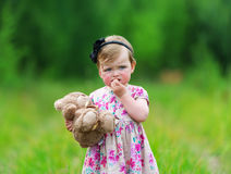 Little girl standing in grass holding large teddy bear. Royalty Free Stock Photography