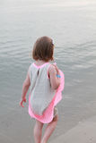 Little girl standing with her back on the sea Stock Photos