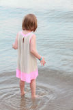 Little girl standing with her back on the sea Royalty Free Stock Photo